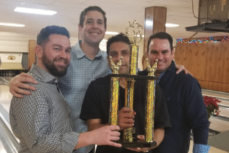 Four men hold trophy after winning the St Louis Lawyers Association Bowling Tournament